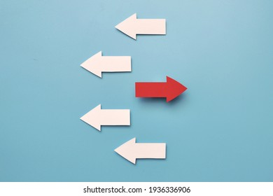 There are many white arrows pointing to the left and one red arrow pointing to the right. A symbol of an innovative, different way in life and business