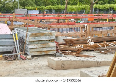 There is a lot of material and tools lying around on a large construction site.