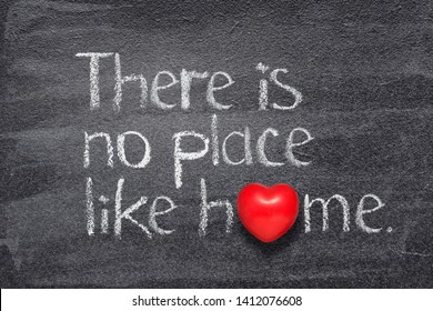 there is no place like home saying written on chalkboard with red heart symbol