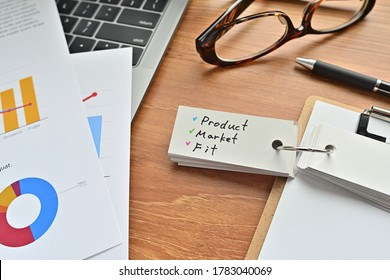 There is a piece of paper with a graph printed on it, a clipboard, and an open vocabulary book on the desk. There is the word Product Market Fit on it.