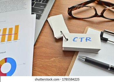 There is a piece of paper with a graph printed on it, a clipboard, and an open vocabulary book on the desk. The word CTR is there. It's an acronym that means Click Through Rate.