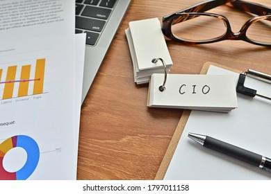 There is a piece of paper with a graph printed on it, a clipboard, and an open vocabulary book on the desk. The word CIO is there. It's an acronym that means chief information officer.