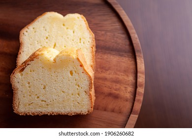 There is a pound cake on the wood tray on the table.