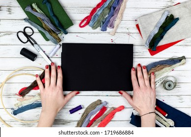 there are quilting, embroidery and sewing tools on the table. patchwork knife, scissors, lined cutting mat, self-locking, threads, measuring tape, floss, hoop. copy space