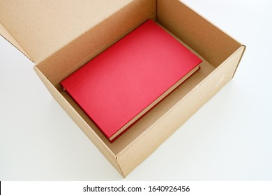 there is a red book in a beige recycled box. book delivery opening of the box with the book