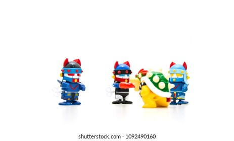 There are robots with three blue helmets on a white background, around a monster with red tongue out.