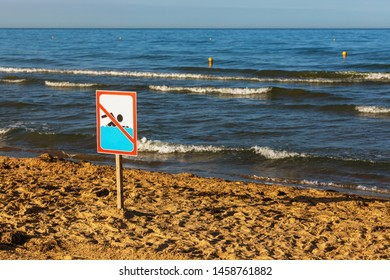 There is a sign on the beach prohibiting swimming due to the storm