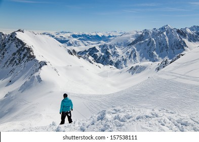 There are snow slopes of mountains from the pass of Tourmalet in the winter Pyrenees. A skier is standing above the downhill.