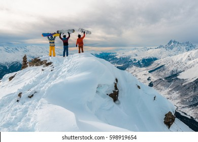 There are three men standing on the top of mountain with snowboards