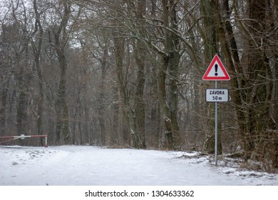 there is warning sign fifty metres befor the barrier on the road in forest in winter with snow on the ground there are trees