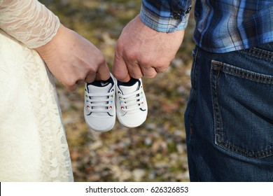 And Then There Were Three - Baby Announcement - Holding Baby Shoes