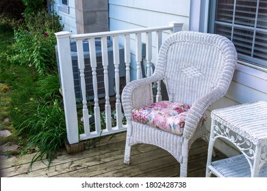 There is a wicker chair with a pillow and a small table in front of the entrance to the house.