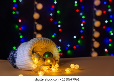 There are winter hat and glowing lights and different colors balls inside the hat are on the table/background. There are the different colors on the background. Merry Christmas. Happy New Year 2020.
