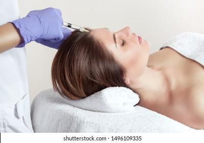Es gibt eine Frau und eine Kosmetologin, die Frau lügt und der Arzt macht das Verfahren der Mesotherapie gegen Haarausfall und Schuppen in einem Schönheitssalon.Strengthen Haar und ihr Wachstum.