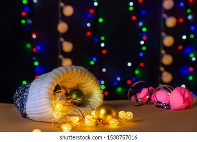 There are wool hat, different colors balls and lights on the table/background. There are pink candy with blue ribbon and different colors lights on the background. Merry Christmas. Happy New Year 2020