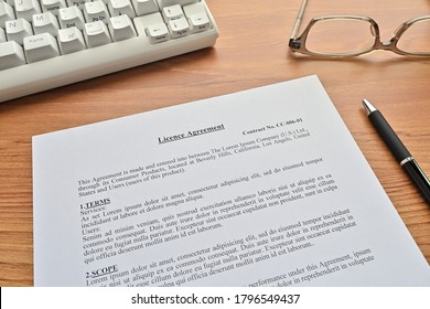 """There's a keyboard, notebook, glasses, and a """"Licence Agreement"""" paper (it's dummy) on the desk."""