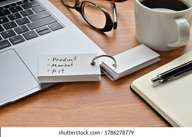 There's a laptop computer, a notebook, a pen and an open vocabulary book on the desk. The word Product Market Fit is written on it.