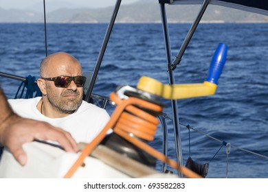 There's a man behind the yellow rope on the boat sailing in the sea