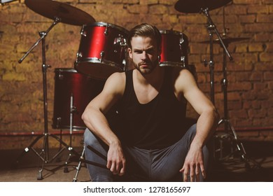 Theres music in the air. Enjoying instrumental music. Handsome man sit on stage at percussion instrument. Man drummer with musical instrument. Rock rehearsal in music club. Rock star or rocker.