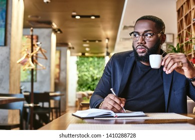 There's no such thing as a free lunch. Portrait of a confident businessman making notes and drinking coffee while resting in the cafe