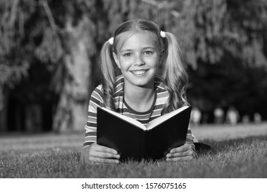 Theres nothing like reading. Happy reader. Cute reader read book on green grass. Small reader enjoy reading. Little reader or bookworm smile on summer landscape. Library and bibliopole concept.