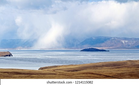 There's snowing under group of clouds, fall into Baikal lake which already turned into ice.