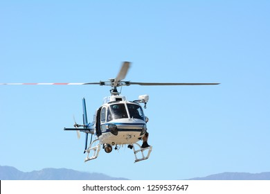 THERMAL, CALIFORNIA - FEBRUARY, 25, 2015: California Highway Patrol Helicopter Crew hovering over the desert during inter-agency training exercises with State Park Rangers.