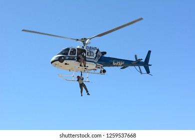 THERMAL, CALIFORNIA - FEBRUARY, 25, 2015: Man being hoisted by cable during California Highway Patrol Helicopter inter-agency training exercise with State Park Rangers.