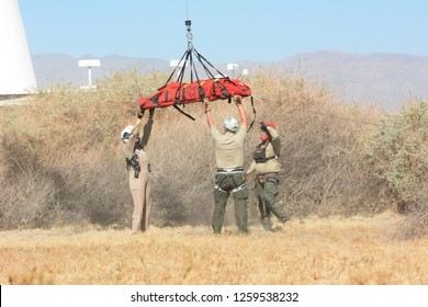 THERMAL, CALIFORNIA - FEBRUARY, 25, 2015: Ground crew guiding litter being airlifted during California Highway Patrol Helicopter inter-agency training exercises with State Park Rangers.