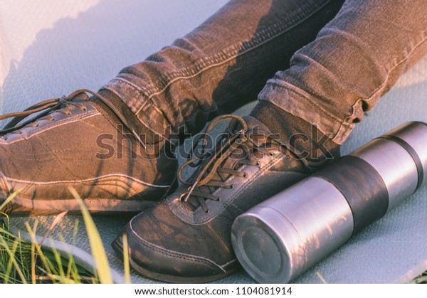 Thermal flask with tea laying on the tourists mat near to the travelers feet in black trainers. Concept of the lunch in journey, traveling, journey, hiking, backpacking.