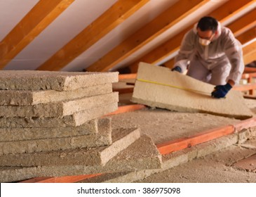 Thermal insulation of a building - mineral wool panels stack with man measuring in the background
