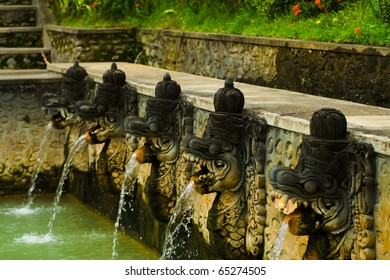 Thermal water shooting into a bathing pool from the mouths of dragon statues at a hot springs in Banjar, Bali, Indonesia. Horizontal