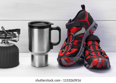 Thermo mug and red shoes for traveling on a light gray background