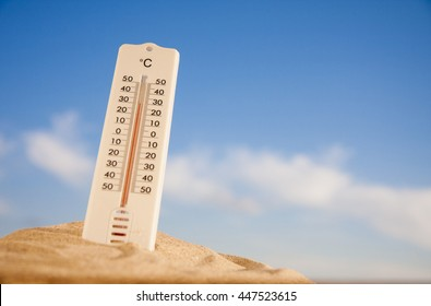 Thermometer with celsius scale on warm beach sand showing high temperature.