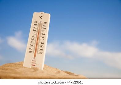 Termómetro con escala celsius en la cálida arena de la playa que muestra alta temperatura.