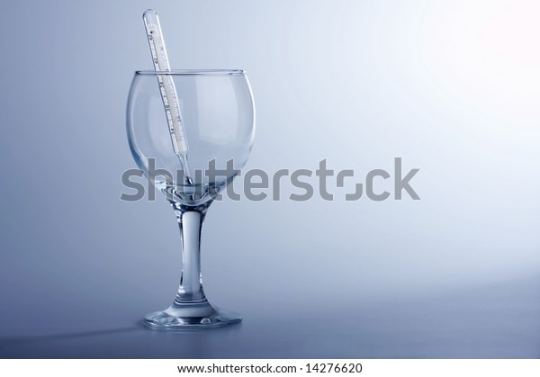 The thermometer in a glass on a blue background