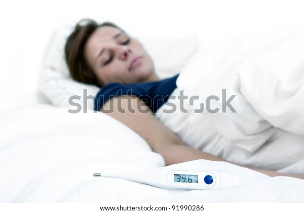 Thermometer, indicating high fever, lying on a bed, with a sick woman in the background