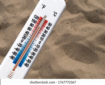 A thermometer lying on a hot sandy beach, reading about 90 degrees Fahrenheit 30 degrees Celcius