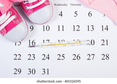 Thermometer for measuring and clothing for newborn on calendar, baby shoes, bodysuits, concept of extending family and expecting for baby