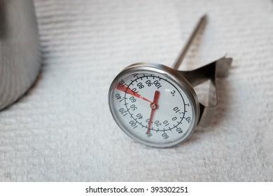 Thermometer for milk frothing from espresso machine resting on paper towel.