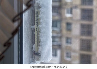 Thermometer a noticeable snow outside the window. Winter