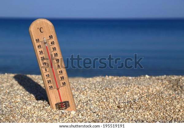 Thermometer on a beach shows high temperatures. Hot weather
