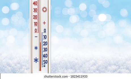 The thermometer on a blurred winter background shows 15 degrees below zero