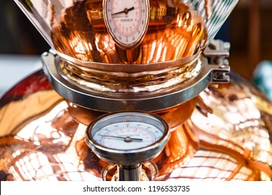 The thermometer on a copper pot for distillation of alcohol