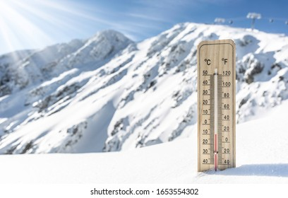 Thermometer on the mountains in the snow shows temperatures ten under zero. Low temperatures in degrees Celsius and fahrenheit.