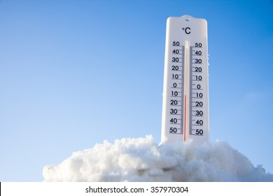 Thermometer on snow shows low temperatures on the sky background
