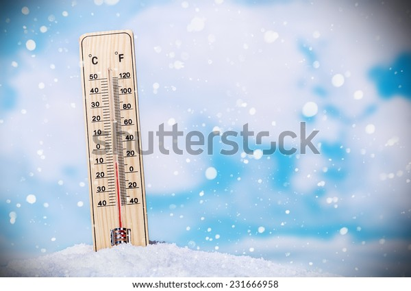 Thermometer on snow shows low temperatures on the sky background with clouds