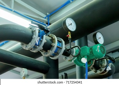Thermometer, pipes and faucet valves of heating system in a boiler room.
