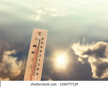 Thermometer showing 30 degrees of heat against the backdrop of lake water with the reflection of clouds and the sun.