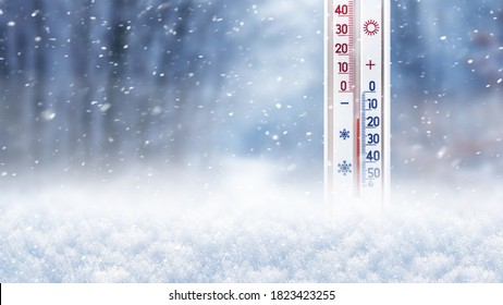 Thermometer in the snow on a background of trees during a snowfall shows 15 degrees below zero